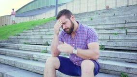 Junger Mann, der auf der Treppe liest Zeitungs-, Schieber- und Wannenschuß sitzt stock video footage