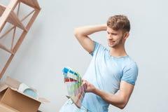 Junger Mann, der auf die neue Platzstellung betrachtet das Palettenlächeln betroffen umzieht lizenzfreies stockbild