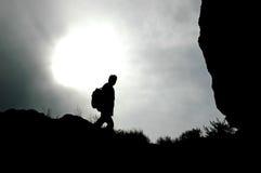 Junger Mann, der auf die Oberseite des Berges geht. Stockbilder