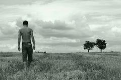 Junger Mann, der auf ein Stubblefeld geht Stockfotos