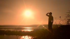Junger Mann, der auf eine Oberseite eines Hügels und aufpassenden der Naturlandschaft klettert stock video footage