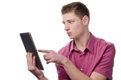 Junger Mann, der auf eine Tablette zeigt. Stockbild