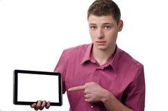 Junger Mann, der auf eine Tablette zeigt. Lizenzfreie Stockfotos