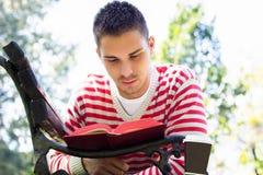 Junger Mann, der auf einem Bank- und Lesebuch liegt Stockfotografie