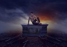 Junger Mann, der auf einem Grab sitzt Stockfoto