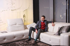 Junger Mann, der auf einem Sofa und einem Lächeln sitzt Stockfotografie