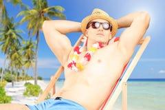 Junger Mann, der auf einem Sonnenruhesessel auf einem Strand nahe bei einem Meer sitzt Stockfotografie