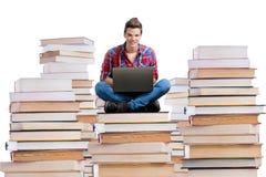 Junger Mann, der auf einem Stapel Büchern mit einem Laptop sitzt lizenzfreie stockfotos