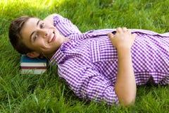 Junger Mann, der auf einem Stapel der Bücher liegt Stockbilder