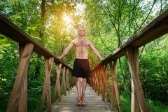 Junger Mann, der auf einem Steg im Wald steht Stockbilder