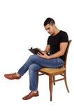 Junger Mann, der auf einem Stuhl betrachtet eine Tablette sitzt Lizenzfreie Stockfotos