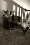 Junger Mann, der auf einem Stuhl sich entspannt Stockfotografie