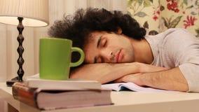 junger Mann, der auf einen Schlaf beim Studieren fällt stock footage