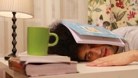 junger Mann, der auf einen Schlaf beim Studieren fällt stock video