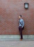 Junger Mann, der auf einer Backsteinmauer sich lehnt Lizenzfreies Stockfoto