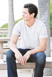 Junger Mann, der auf einer Bank sitzt stockfotografie