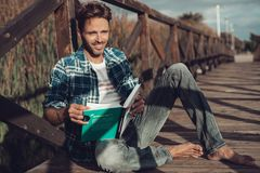 Junger Mann, der auf einer Brücke sitzt stockfotos