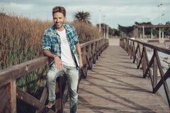 Junger Mann, der auf einer Brücke steht Lizenzfreies Stockfoto