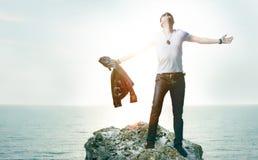 Junger Mann, der auf einer Klippe glücklich steht Lizenzfreies Stockbild