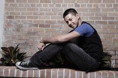 Junger Mann, der auf einer Leiste sitzt Stockfotos
