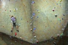 Junger Mann, der auf einer steigenden Wand steigt. Lizenzfreie Stockfotografie