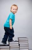 Junger Mann, der auf einer Strichleiter der Bücher steigt Stockfotografie