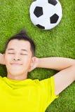 Junger Mann, der auf einer Wiese liegt Lizenzfreie Stockfotografie