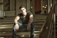 Junger Mann, der auf eleganter Treppe sitzt Stockbild