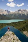 Junger Mann, der auf Fluss-Stein über Seen steht stockfotos