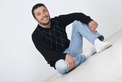 Junger Mann, der auf Fußboden sitzt Lizenzfreie Stockfotos