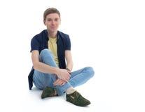 Junger Mann, der auf Fußboden sitzt Lizenzfreie Stockfotografie