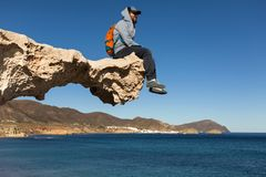 Junger Mann, der auf gemeißelter Felsenstruktur, Los Escullos, Spanien sitzt lizenzfreie stockfotos