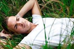 Junger Mann, der auf grünen gras liegt lizenzfreies stockfoto