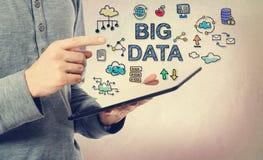 Junger Mann, der auf großes Datenkonzept über einer Tablette zeigt Stockbilder