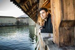 Junger Mann, der auf hölzernem Steg in der Schweiz beim weg schauen steht Lizenzfreie Stockfotos