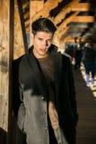 Junger Mann, der auf hölzernem Steg in der Schweiz beim weg schauen steht Stockfotografie