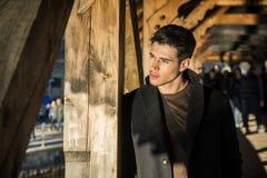 Junger Mann, der auf hölzernem Steg in der Schweiz beim weg schauen steht Stockbilder