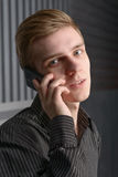Junger Mann, der auf Handy spricht stockfotografie