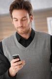 Junger Mann, der auf Handy texting ist Stockbild