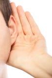 Junger Mann, der auf Klatsch hört Stockbild