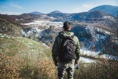 Junger Mann, der auf Klippe in den Winterbergen halten a steht stockbild