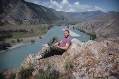 Junger Mann, der auf der Klippe sitzt und auf dem Tal schaut Trekking in den Bergen lizenzfreie stockfotografie