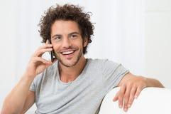 Junger Mann, der auf Mobiltelefon spricht Stockfotos