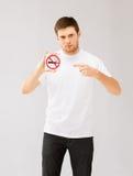 Junger Mann, der auf Nichtraucherzeichen zeigt Stockfotografie