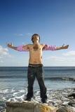 Junger Mann, der auf Ozean-Felsen mit den Armen Outstre steht Stockfotos