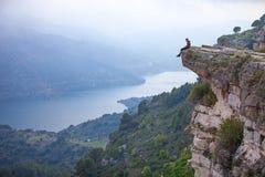 Junger Mann, der auf Rand der Klippe sitzt Stockbilder