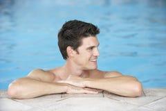 Junger Mann, der auf Rand des Swimmingpools stillsteht Stockfoto