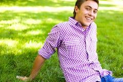 Junger Mann, der auf Rasen sitzt Stockfotos