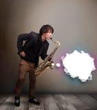 Junger Mann, der auf Saxophon mit Kopienraum in der weißen Wolke spielt Stockfotografie