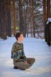 Junger Mann, der auf Schnee sitzt lizenzfreie stockfotos